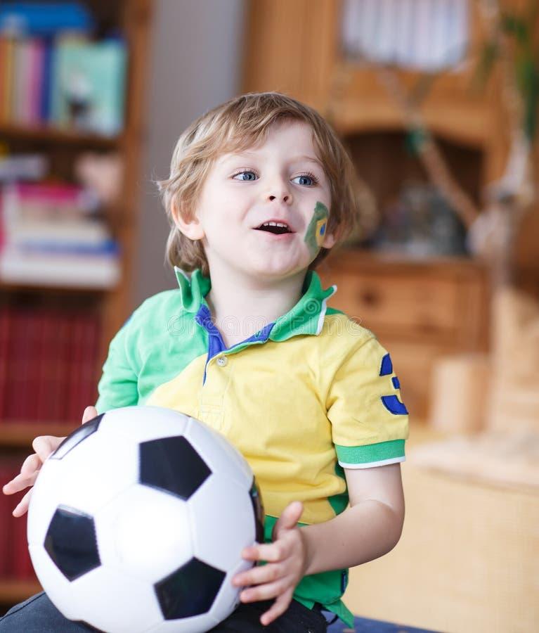 Mała blond preschool chłopiec 4 roku z futbolowym przyglądającym socc obraz royalty free