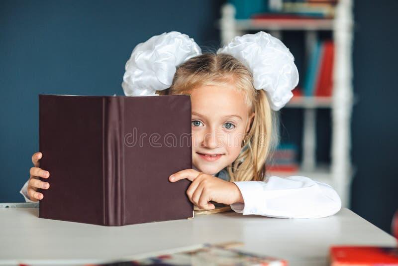 Mała blondynki dziewczyna ono chuje za książką, studiowanie, kocha uczyć się Śliczna mała dziewczynka chuje za książką obrazy royalty free
