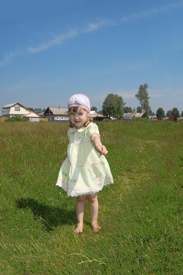 Mała bosa dziewczyna bawić się przedstawienia ostrze trawa fotografia royalty free