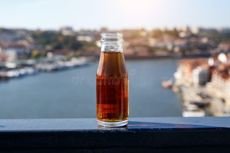 Mała butelka portowy wino przy plenerowym z Douro rzeką Porto miastem w tle i zdjęcie royalty free