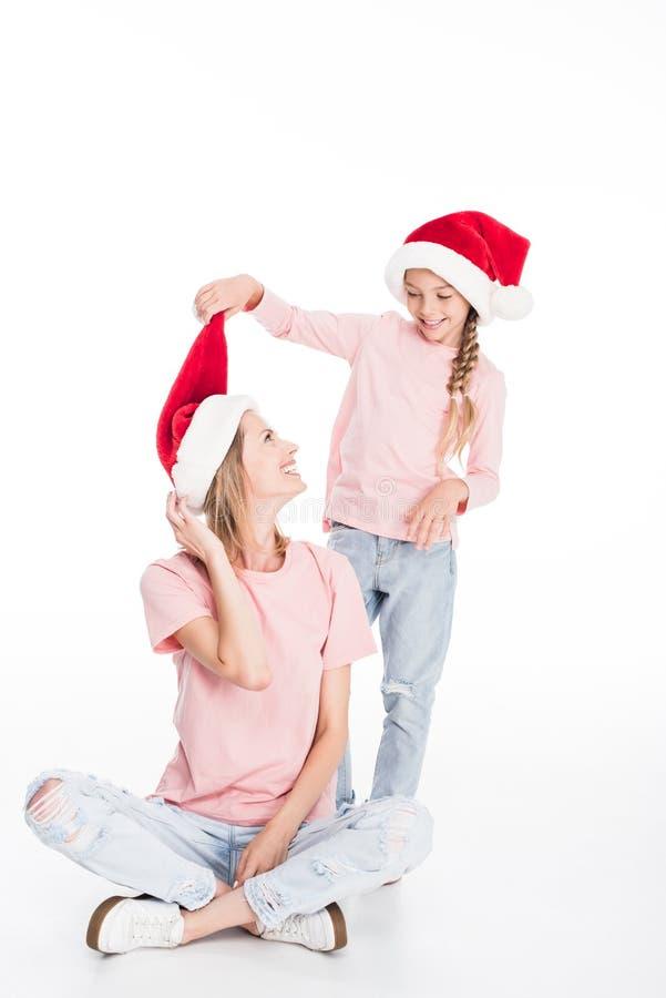 Mała córka bawić się z jej matką ciągnąć jej Santa kapelusz daleko, fotografia royalty free