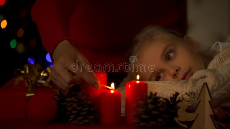 Mała córka patrzeje jak matek oświetleniowe Bożenarodzeniowe świeczki, wiara w cudzie obraz royalty free