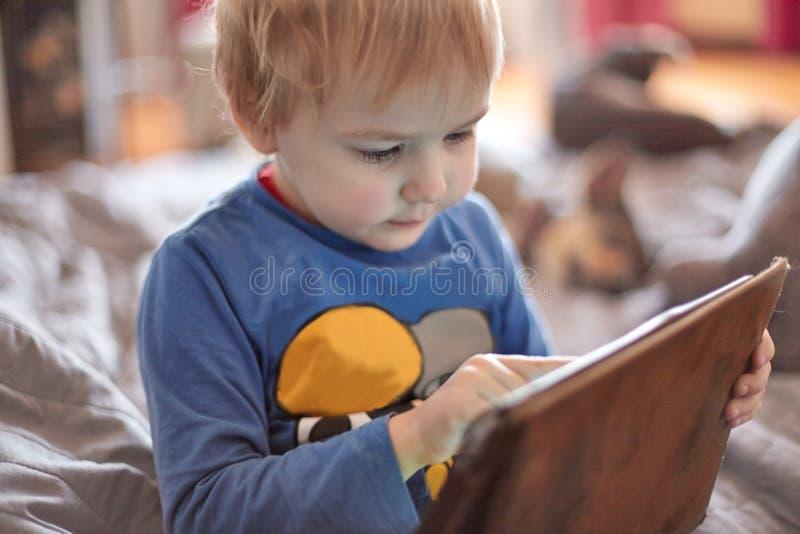 Mała caucasian chłopiec siedzi na kanapie używać pastylkę, dotyka ekran Czerwony włosy, przypadkowa odzież, indoors, zakończenie  obrazy royalty free