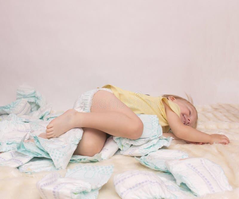 Mała caucasian dziewczyna bawić się z pieluszkami na białym tle, pielucha, kopii przestrzeń zdjęcie royalty free