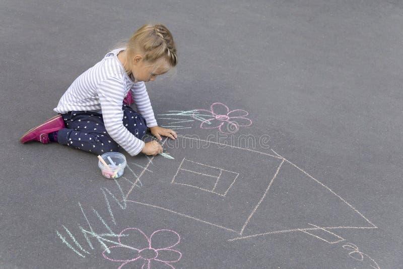 Mała caucasian dziewczyna rysuje dom z pisze kredą fotografia stock