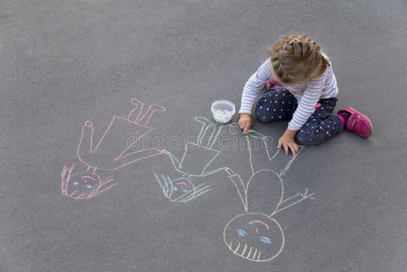 Mała caucasian dziewczyna rysuje szczęśliwej rodziny z pisze kredą na bruku obraz stock