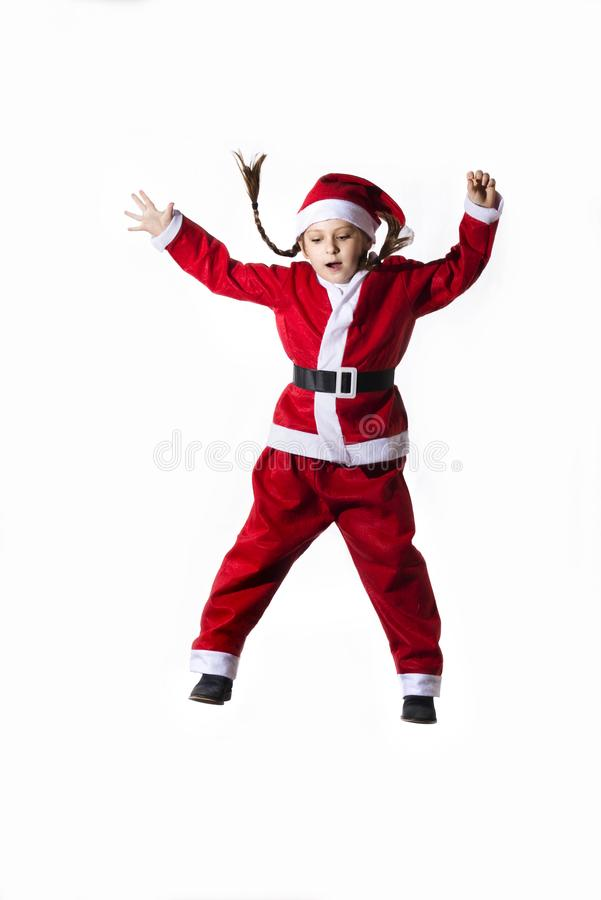 Mała caucasian dziewczyna ubierał jako Święty Mikołaj doskakiwanie na białym tle zdjęcia stock