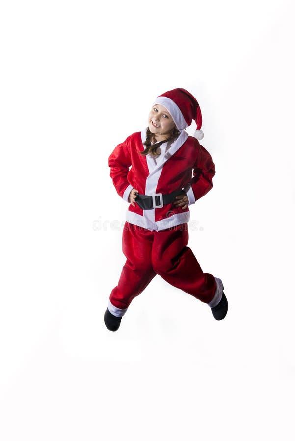 Mała caucasian dziewczyna ubierał jako Święty Mikołaj doskakiwanie na białym tle zdjęcie stock