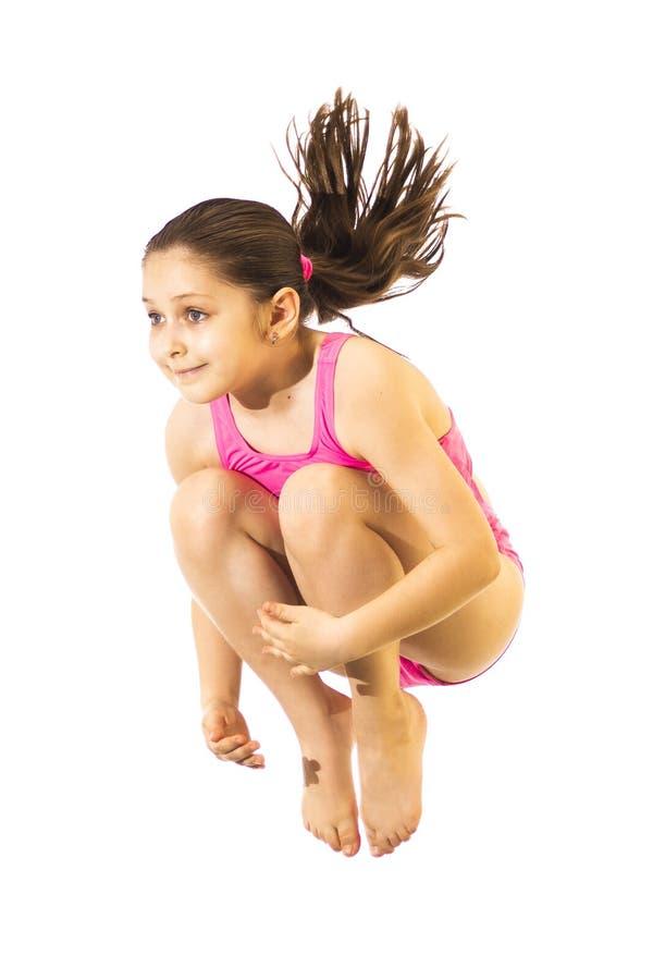 Mała caucasian kobiety 8 lat dziewczyna w różowym swimmwear doskakiwaniu na białym tle fotografia stock