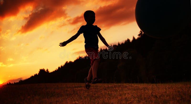 Mała chłopiec bawić się piłkę na polu zdjęcia stock