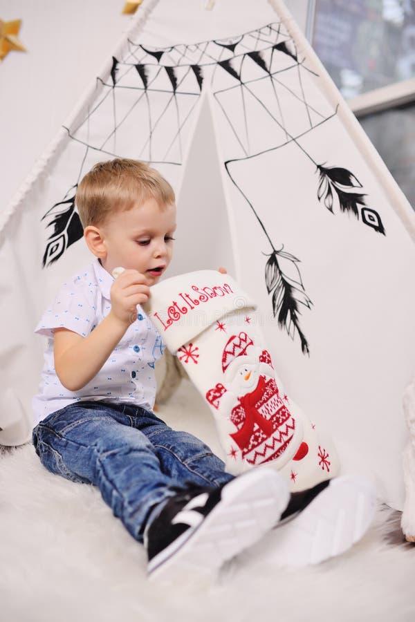 mała chłopiec bierze out teraźniejszość od Bożenarodzeniowej skarpety przeciw tłu namiot lub Indiański wigwam obraz stock