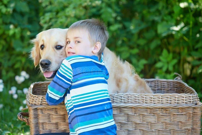 Mała chłopiec i śliczny pies w koszu fotografia royalty free