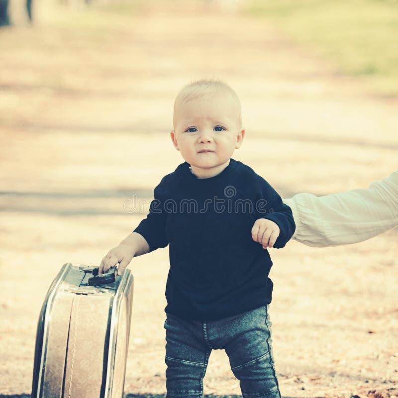 Mała chłopiec niesie retro walizkę na naturalnym krajobrazie Dziecko podróż dla wakacje z torbą z matki ręką Dzieciaka podróżnik obrazy royalty free