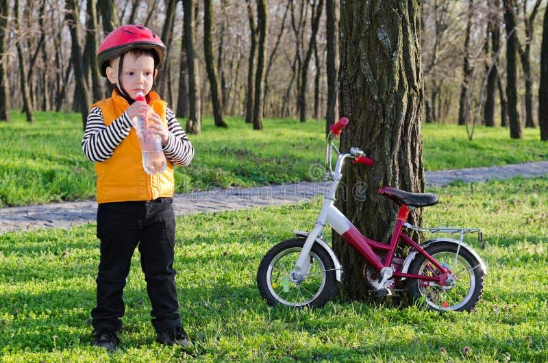 Mała chłopiec pije wodę butelkową zdjęcie royalty free