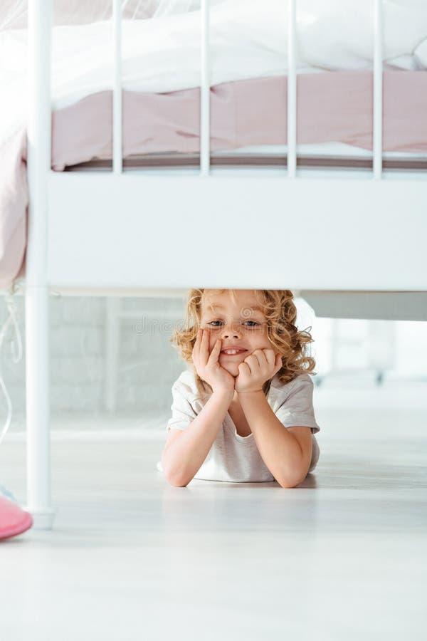 Mała chłopiec pod łóżkiem zdjęcia stock