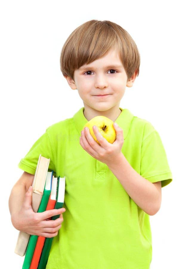 Mała chłopiec z jabłkiem i książkami zdjęcia stock