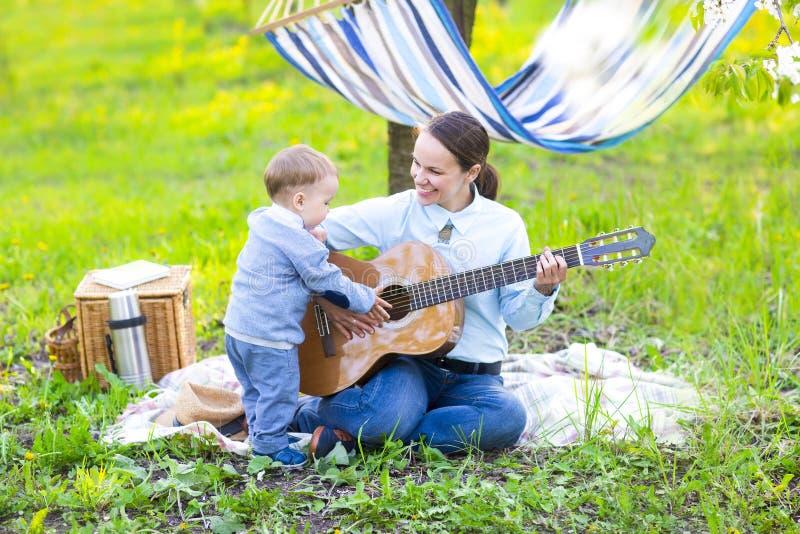 Mała chłopiec z matką w kwitnie ogródzie obraz stock