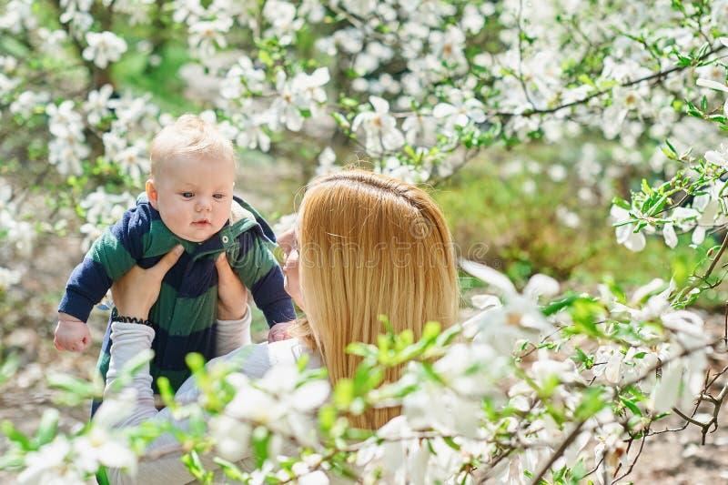 Mała chłopiec z potomstwo matką w wiosny okwitnięcia ogródzie obrazy royalty free