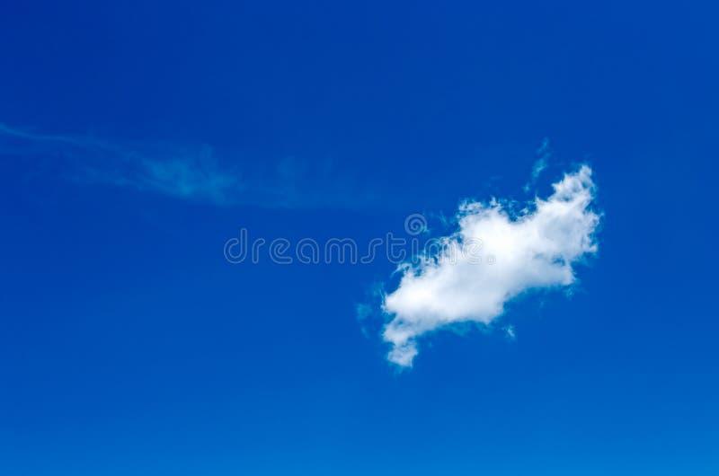 Mała chmura krzyżuje niebieskie niebo zdjęcia stock