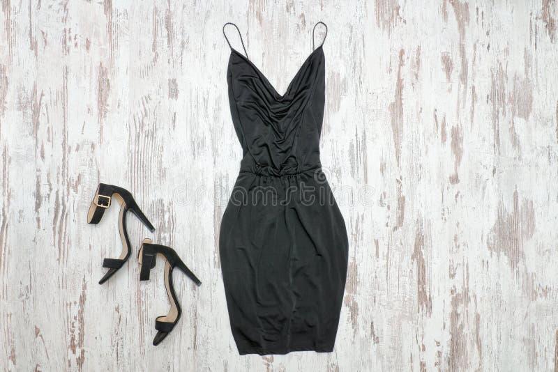 Mała czerni suknia, buty i Drewniany tło, modny przeciw fotografia royalty free