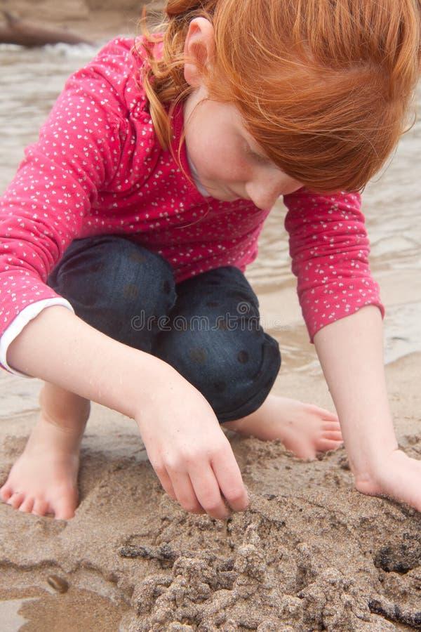 Mała czerwona z włosami dziewczyna buduje piaska kasztel z mokrym piaskiem przy a obrazy royalty free