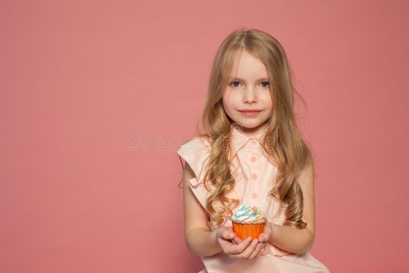 Mała dziewczyna w ręce trzyma słodkiego babeczka torta cukierek fotografia stock