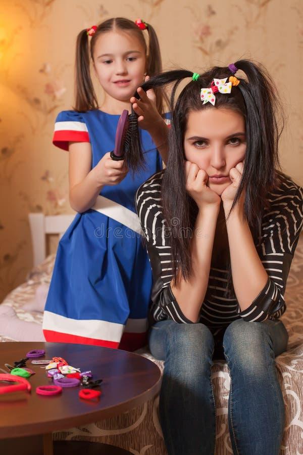 Mała dziewczynka bawić się fryzjera z jej matką fotografia stock