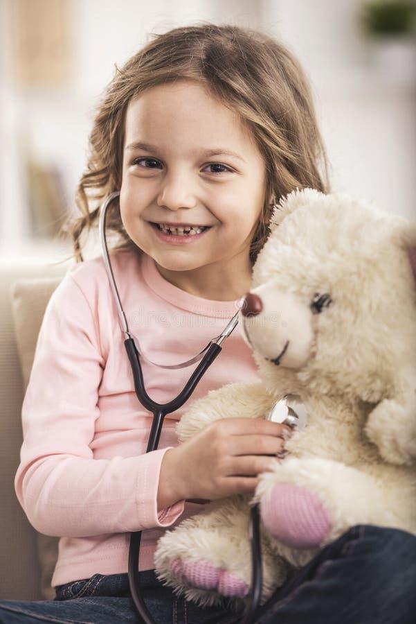 Mała dziewczynka bawić się lekarkę z misiem zdjęcie stock