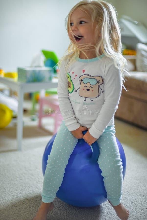 Mała dziewczynka bawić się na pełen wigoru piłce zdjęcie stock