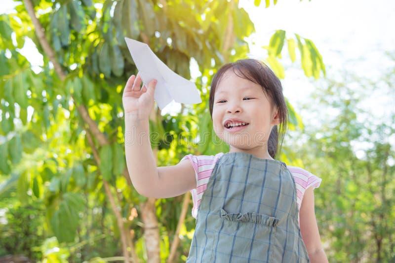 Mała dziewczynka bawić się papierowego samolot fotografia stock