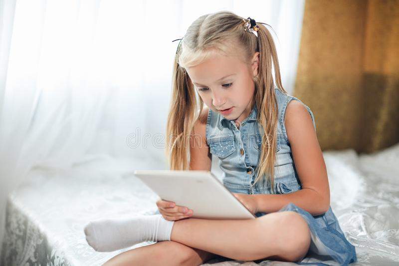 Mała dziewczynka bawić się pastylkę zdjęcia stock