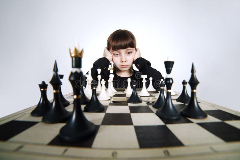 Mała dziewczynka bawić się szachy na bielu zdjęcie stock