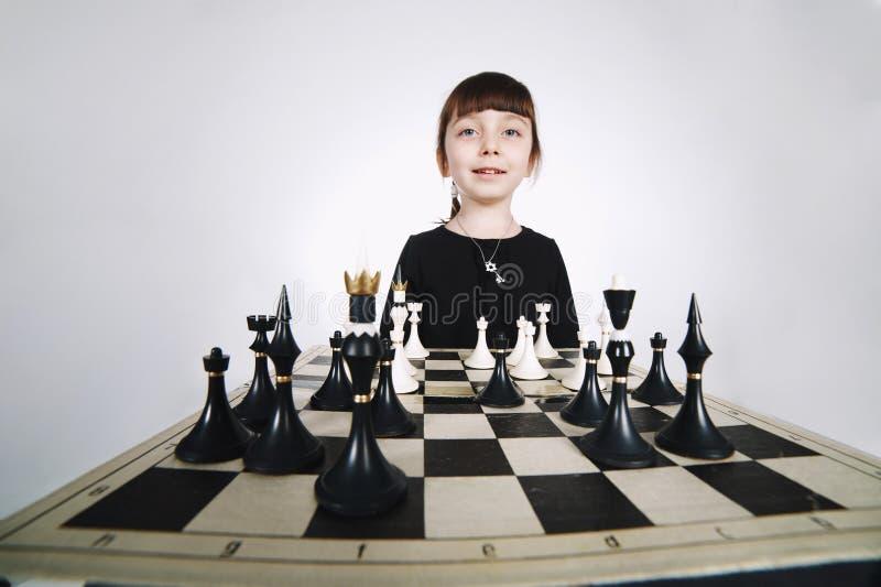 Mała dziewczynka bawić się szachy na bielu fotografia stock