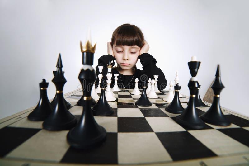Mała dziewczynka bawić się szachy na bielu obraz stock