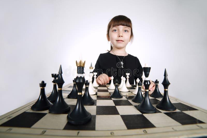 Mała dziewczynka bawić się szachy na bielu zdjęcia stock