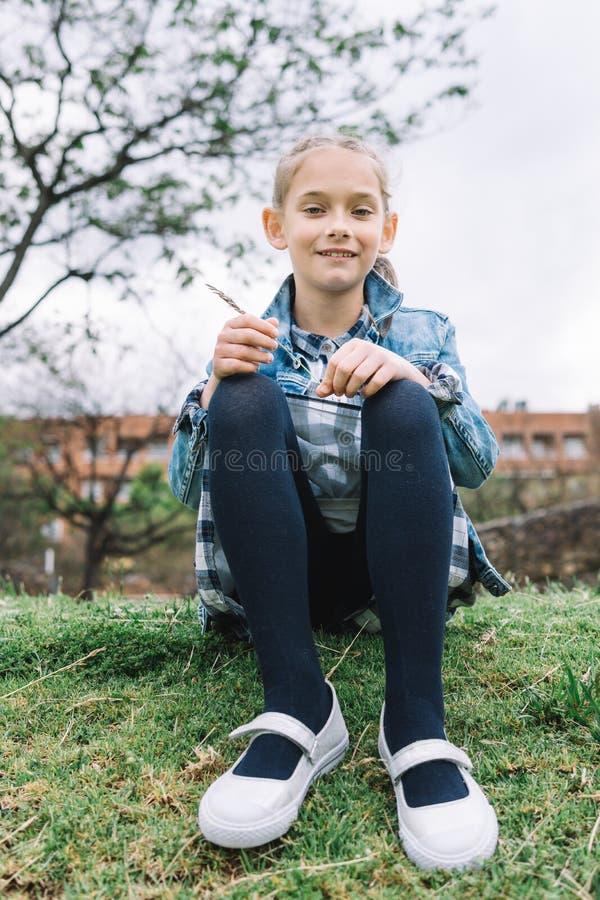 Mała dziewczynka bawić się w parku w zielonym tle fotografia stock