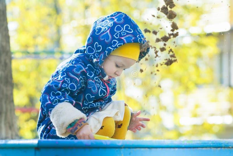 Mała dziewczynka bawić się w piaskownicie outdoors przy jesieni żółtym shrubbery i drzewo liści tłem obraz stock