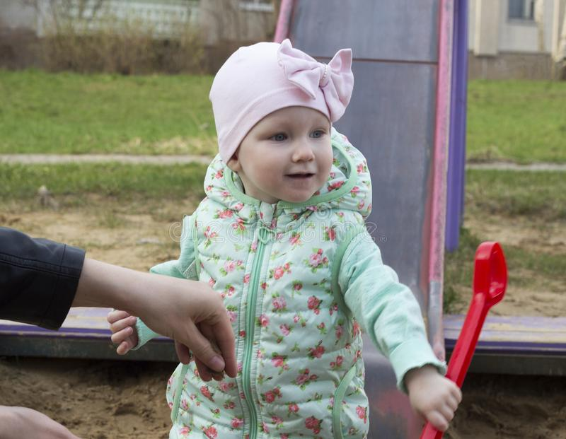 Mała dziewczynka bawić się w piaskownicie z czerwonym scapula małym obraz royalty free