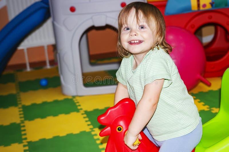 Mała dziewczynka bawić się w rozrywki centrum Szczęśliwy dziecko z zabawkami obraz stock