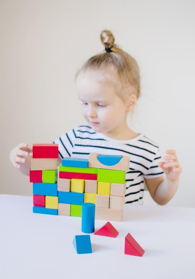 Mała dziewczynka bawić się z drewnianymi kolorowymi sześcianami w domu fotografia royalty free