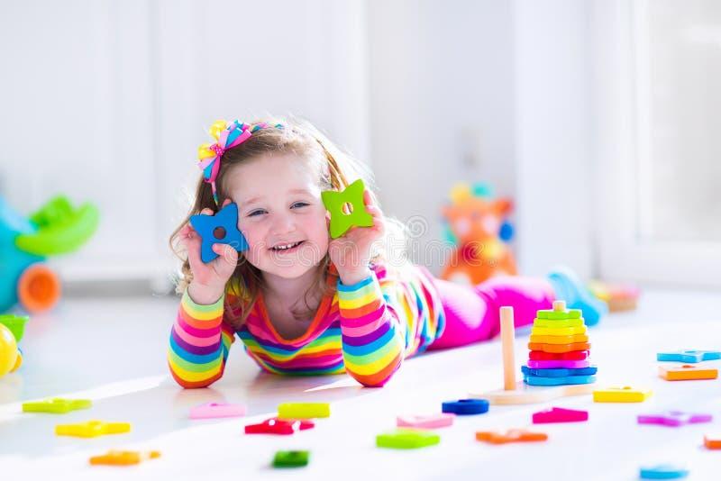 Mała dziewczynka bawić się z drewnianymi zabawkami zdjęcia royalty free