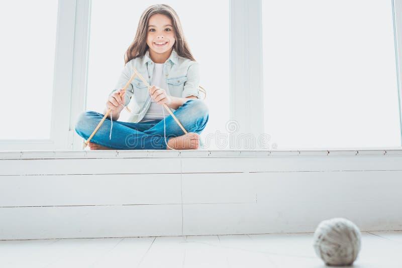 Mała dziewczynka bawić się z dzianiem wtyka siedzącego pobliskiego okno obraz stock