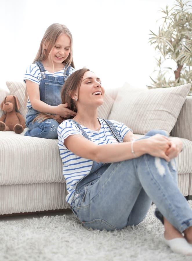 Mała dziewczynka bawić się z jej matką w fryzjerze zdjęcia royalty free