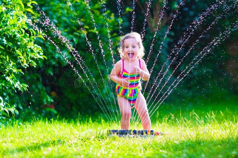 Mała dziewczynka bawić się z ogród wody kropidłem fotografia stock