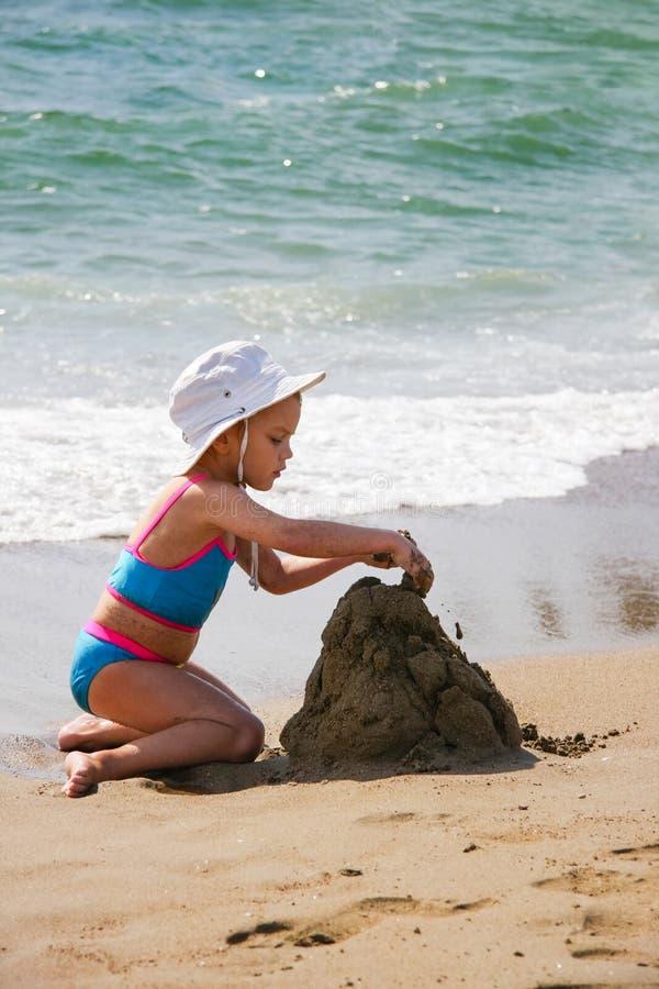 Mała dziewczynka bawić się z piaskiem na plaży zdjęcia royalty free