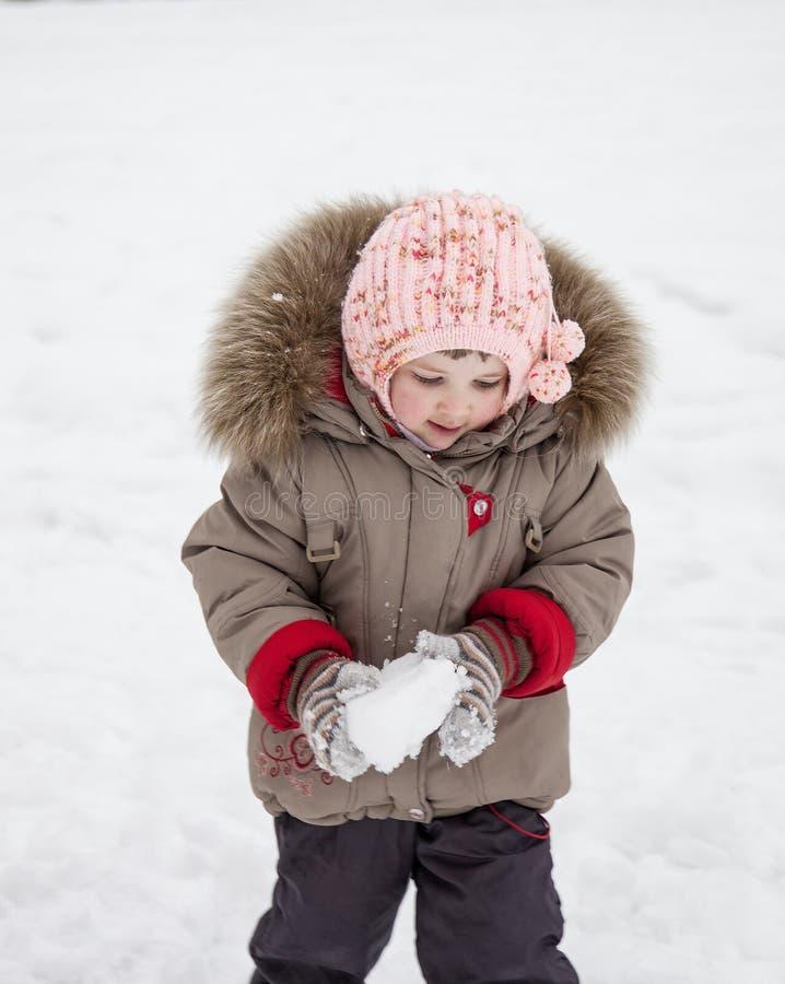 Mała dziewczynka bawić się z snowballs zdjęcie royalty free