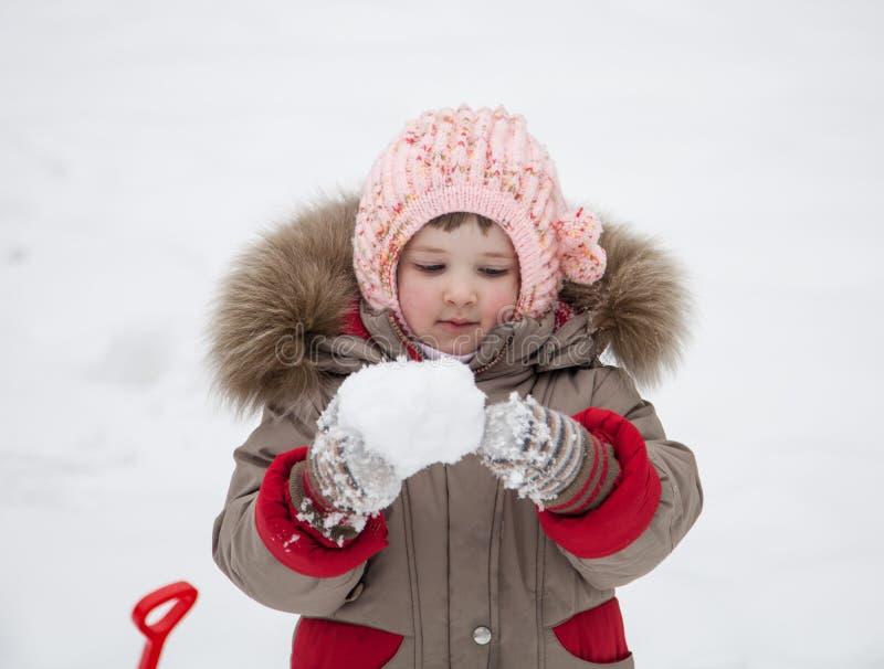 Mała dziewczynka bawić się z snowballs zdjęcia stock
