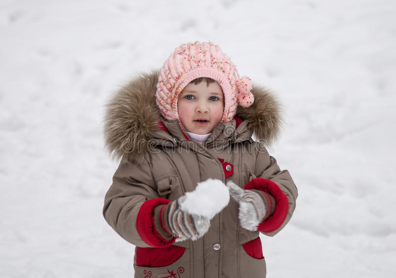 Mała dziewczynka bawić się z snowballs zdjęcie stock