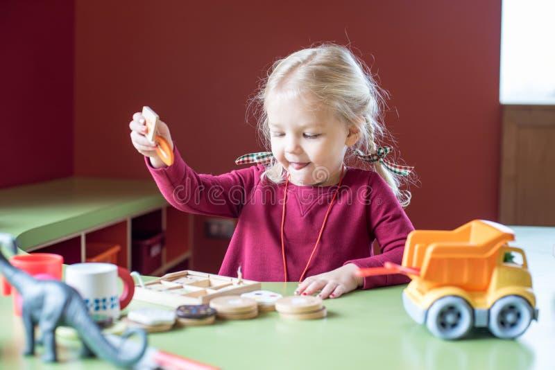 Mała dziewczynka bawić się z zabawkami przy bibliotecznym uczenie centrum zdjęcia stock