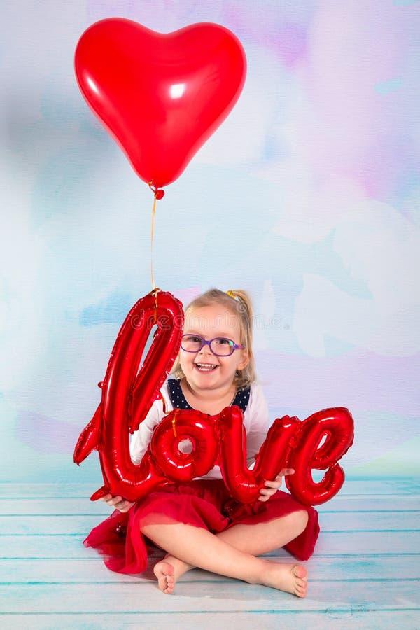 Mała dziewczynka berbeć z czerwonym kierowym balloonand miłości znakiem t?a b??kitny pude?ka poj?cia konceptualny dzie? prezenta  zdjęcie stock